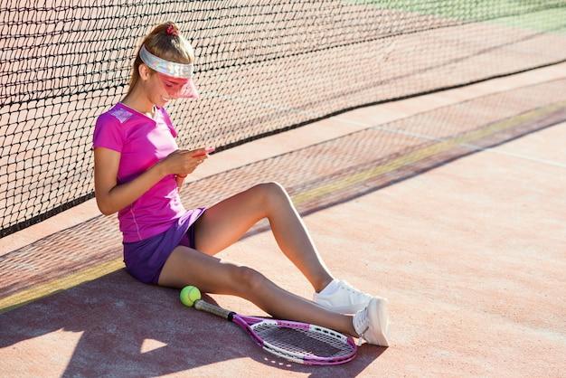 Tiro de zorra de menina desportiva, sentado em um campo de tênis perto da rede e usa telefone inteligente para conversar e surfar em redes sociais no fundo por do sol.