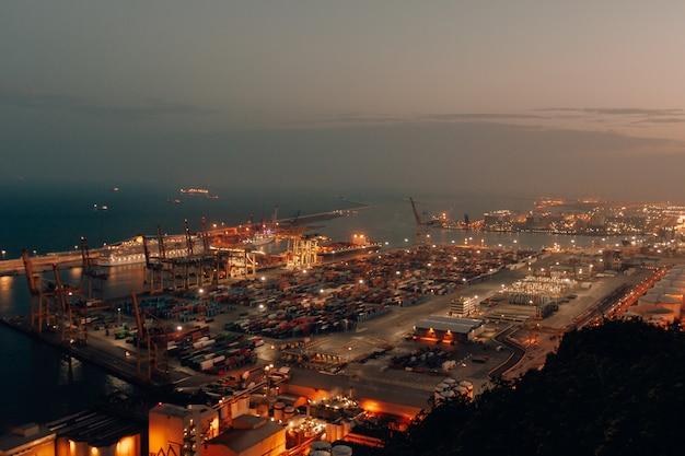 Tiro distante de um porto com barcos carregados de carga e remessa durante a noite