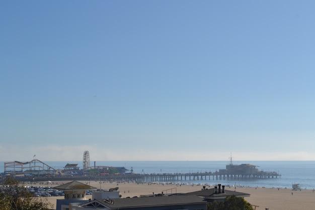 Tiro distante distante de um parque de diversões em uma doca à beira-mar sob um céu azul claro
