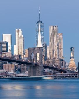Tiro distante vertical da ponte do brooklyn sobre o corpo de água perto de arranha-céus em nova york
