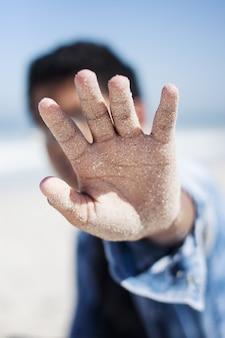 Tiro do close up do foco seletivo da palma arenosa de um homem que cobre sua cara na praia