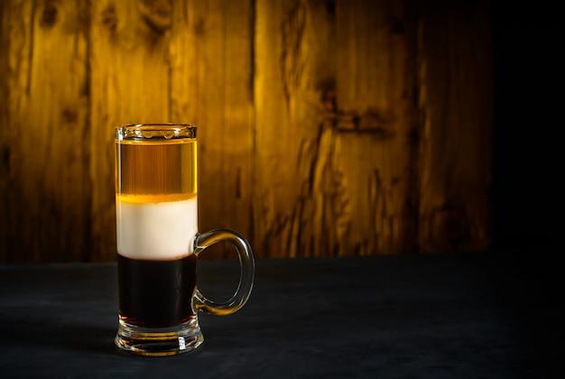 Tiro do cocktail do álcool b52 na madeira.