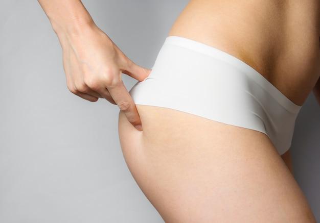 Tiro do estúdio de beleza. mulher magra em calcinha branca toca suas nádegas elásticas em cinza. cortar foto