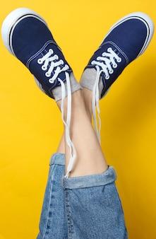 Tiro do estúdio de moda. pernas femininas levantadas em jeans e tênis com atacadores desamarrados em amarelo.