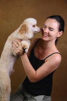Tiro do estúdio de uma jovem mulher bonita que sorri e que guarda o cão de caniche branco do anão lindo.