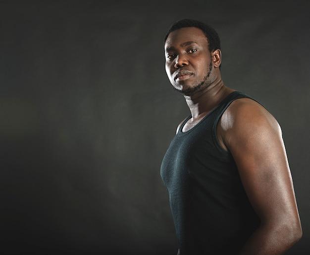 Tiro do estúdio do homem afro-americano novo com barba e camiseta de alças sobre o fundo preto.