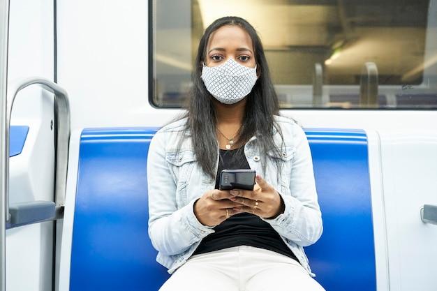 Tiro do meio de uma mulher negra sentada no vagão do metrô, olhando para uma câmera segurando um smartphone.