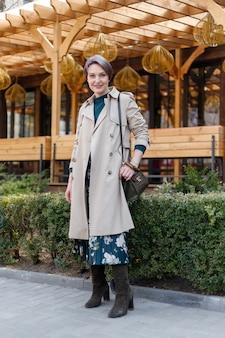 Tiro do retrato de uma mulher atraente e elegante atalho, garota caminha ao ar livre da cidade. imagem elegante, moderna e feminina, estilo. menina com uma capa ou casaco bege e um vestido verde Foto Premium