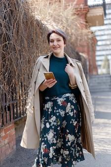 Tiro do retrato de uma mulher atraente e elegante atalho, garota caminha ao ar livre da cidade. imagem elegante, moderna e feminina, estilo. menina com uma capa ou casaco bege e um vestido verde