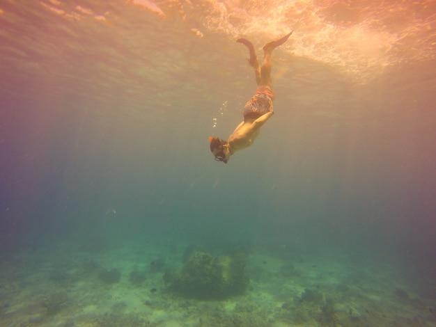 Tiro do selfie subaquático com um jovem que mergulha em um sopro de respiração em um mar tropical sobre o fundo arenoso. profundo mar azul. grande angular. vintage filtrou a imagem.