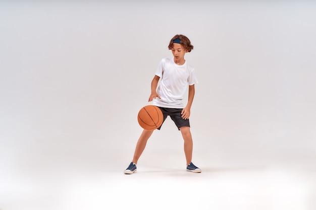 Tiro em comprimento total de competição de um adolescente jogando basquete em pé isolado sobre o cinza
