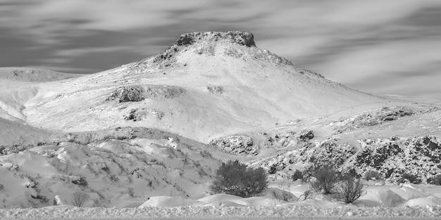 Tiro em escala de cinza ampla de colinas nevadas e uma montanha à distância com um céu nublado