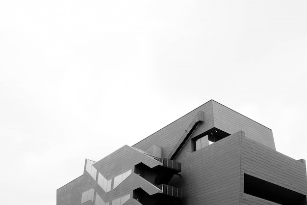 Tiro em escala de cinza de ângulo baixo de um edifício moderno concreto isolado em uma parede branca
