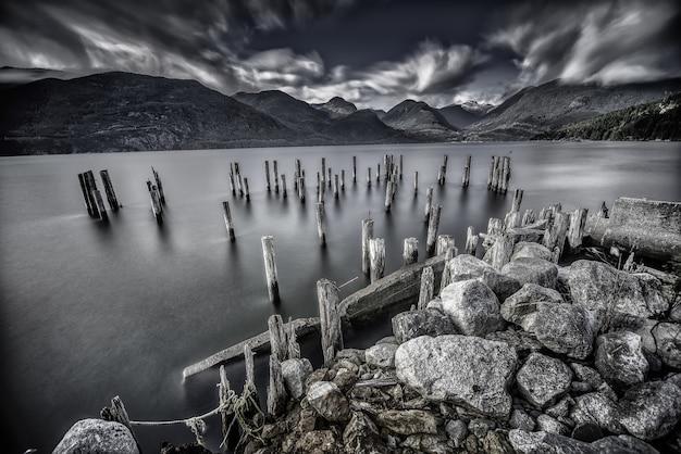 Tiro em escala de cinza de árvores registra um lago cercado por enormes rochas e belas montanhas