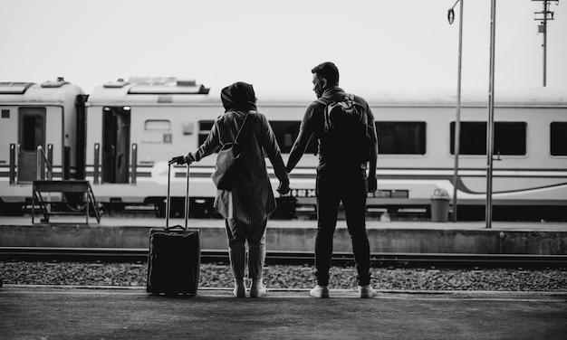 Tiro em escala de cinza de um casal em pé em uma estação de trem