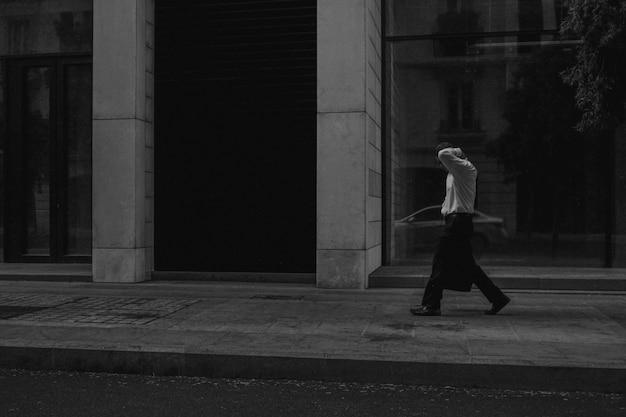 Tiro em escala de cinza de um homem andando por uma zona de pedestres perto de um prédio
