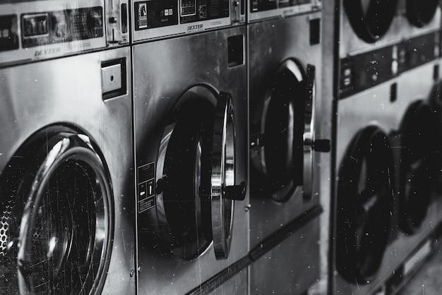 Tiro em escala de cinza de uma máquina de lavar com portas abertas