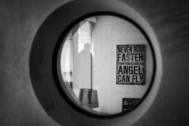Tiro em escala de cinza de uma sinalização de citação motivacional na parede vista através de uma janela redonda