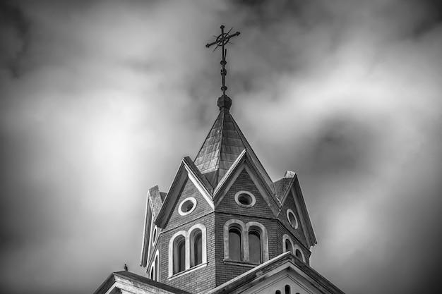 Tiro em escala de cinza em ângulo baixo do topo de uma igreja cristã com céu nublado