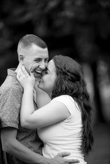 Tiro em escala de cinza vertical de um casal branco feliz, curtindo a companhia um do outro