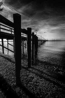 Tiro em escala de cinza vertical de uma doca de madeira com colunas no lago sob as belas nuvens de tempestade