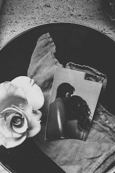 Tiro em escala de cinza vertical de uma fotografia de dois amantes ao lado de uma flor em um balde