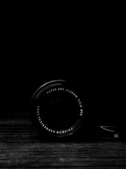 Tiro em escala de cinza vertical de uma lente de câmera em uma superfície de madeira