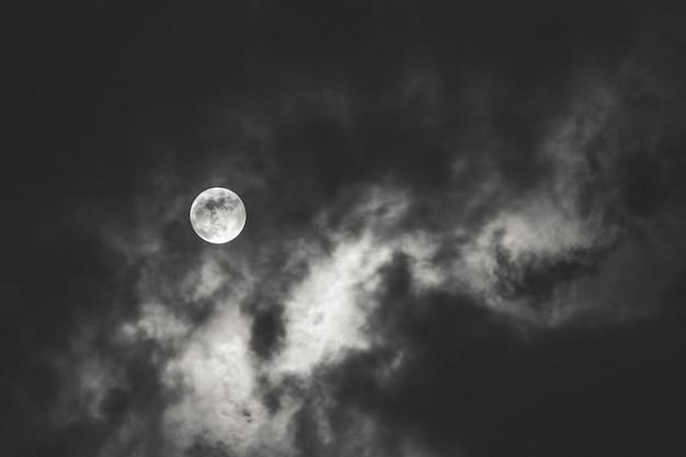 Tiro escuro da lua cheia espalhando luz atrás das nuvens durante a noite