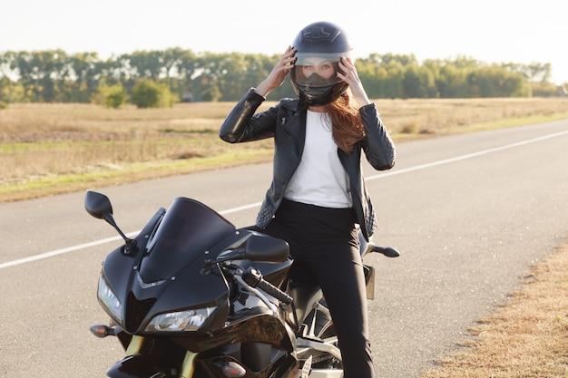 Tiro externo de motociclista feminina rápida usa capacete protetor, posa em moto, fica em moto, cobre longa distância, tem viagem inesquecível. pessoas, equitação, segurança e conceito extremo