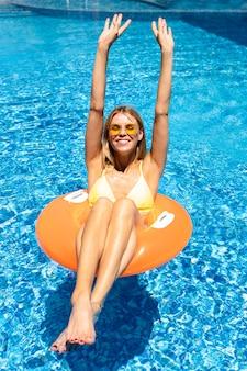 Tiro feliz mulher feliz na piscina