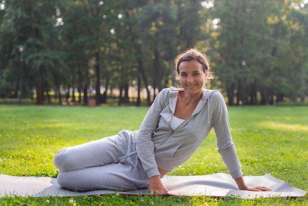 Tiro feliz mulher feliz sentado no tapete de ioga