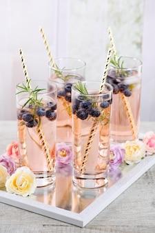 Tiro frio em vidro com mirtilo, cubos de gelo, alecrim. inspiração para comemorar no estilo provençal