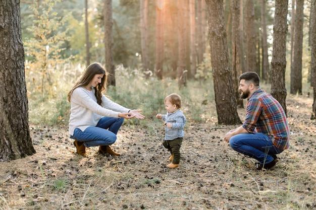 Tiro horizontal ao ar livre da bela jovem família caucasiana em uma caminhada na floresta de outono. bebezinho criança andando de seu pai para a mãe e rindo