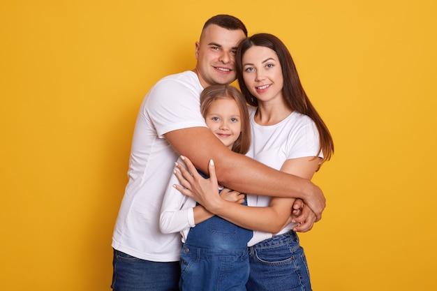 Tiro horizontal da bela jovem família abraçando
