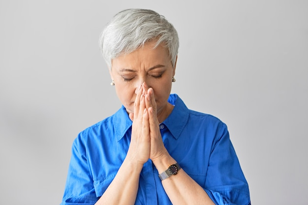 Tiro horizontal da linda mulher aposentada elegante de cabelos grisalhos na camisa azul, fechando os olhos e segurando o rosto de mãos dadas, preocupando-se com seu filho problemático. senhora madura cobrindo a boca enquanto espirra