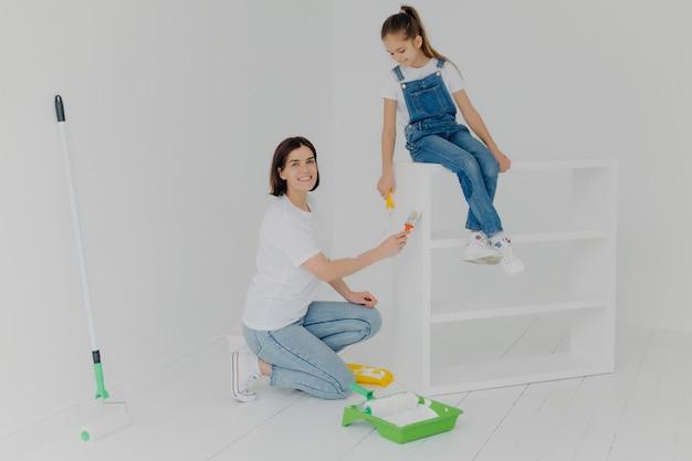Tiro horizontal da mãe carinhosa e sua filha ocupada reformando móveis em casa