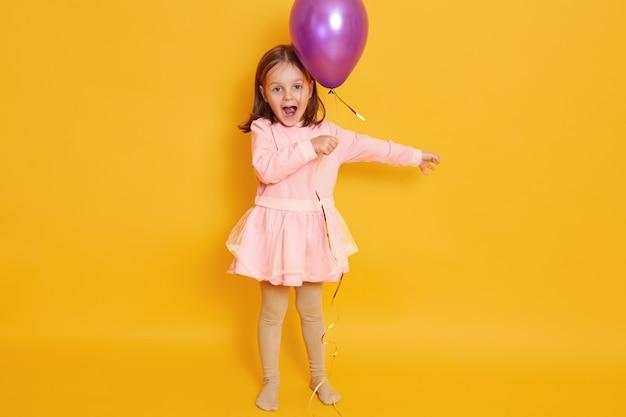 Tiro horizontal da menina com balão roxo isolado sobre o amarelo toda criança do sexo feminino gritando algo, comemorando o dia da criança, garoto usando vestido rosado e cabelo escuro.