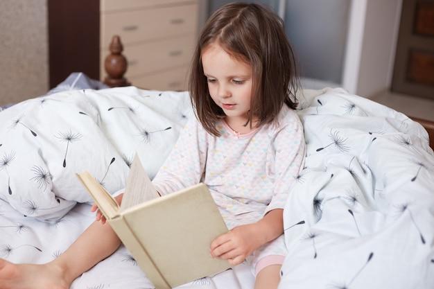 Tiro horizontal da menina sentada em sua cama e lendo livro interessante, criança do sexo feminino vestindo pijama branco, passando o tempo livre em seu quarto aconchegante, parece concentrado. conceito de educação de crianças.