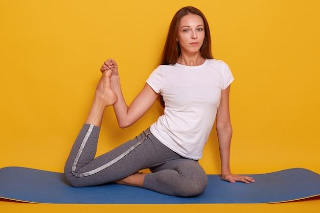 Tiro horizontal da mulher desportiva magro, fazendo exercícios de alongamento no ginásio