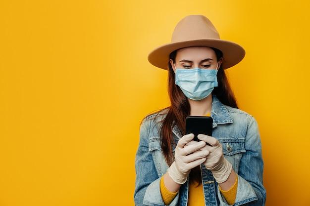 Tiro horizontal da mulher em luvas estéreis médicas de máscara facial, bate-papo online com amigos, verifica a notificação recebida no e-mail, estando sempre em contato, usa jaqueta jeans. conceito de coronavírus pandêmico