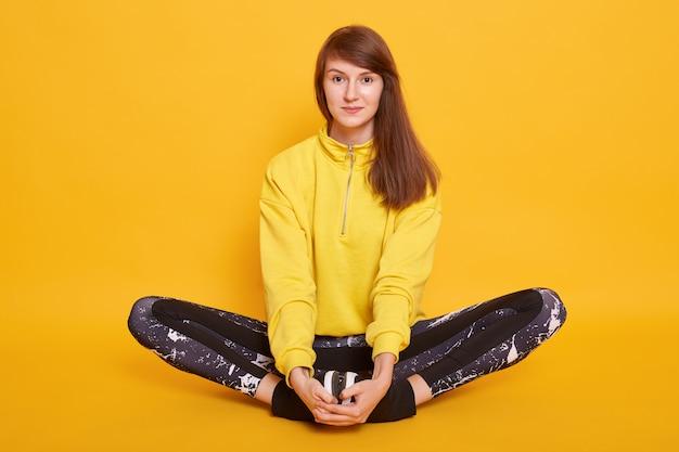 Tiro horizontal da mulher jovem e atraente meditando enquanto está sentado no estúdio floorin