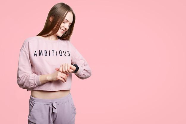 Tiro horizontal da mulher magro alegre olha smartwatch, espera por alguém ou controla suas calorias após treino, posa contra parede rosa com espaço de cópia para o seu texto promocional.