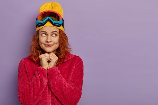 Tiro horizontal da sonhadora menina ruiva com covinhas nas bochechas, usa roupas de inverno e máscara de esqui, isolada sobre a parede roxa.