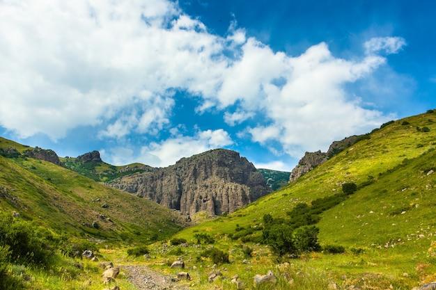 Tiro horizontal das montanhas cobertas de verde sob o lindo céu nublado