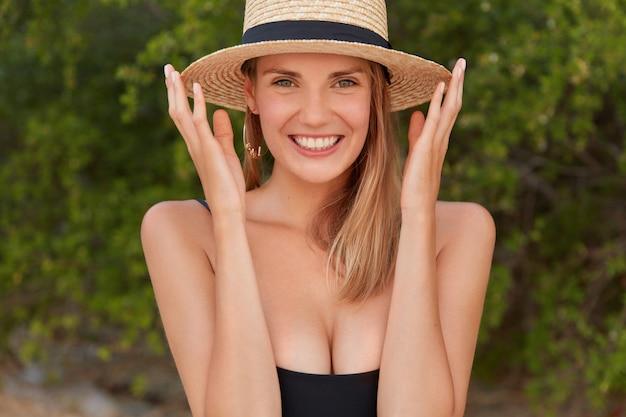 Tiro horizontal de agradável procura jovem turista feminina com chapéu de palha e maiô, tem um sorriso largo, dentes brancos perfeitos, satisfeita com as férias de verão na praia tropical.