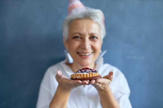 Tiro horizontal de alegre fêmea madura positiva com cabelos grisalhos, aproveitando a festa de aniversário, comendo torta de amora. foco seletivo no bolo