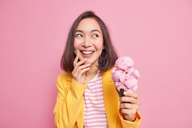 Tiro horizontal de alegre morena jovem mulher asiática desvia o olhar de bom grado detém delicioso sorvete frio em waffle usa roupas elegantes goza de férias de verão isoladas sobre parede rosa.