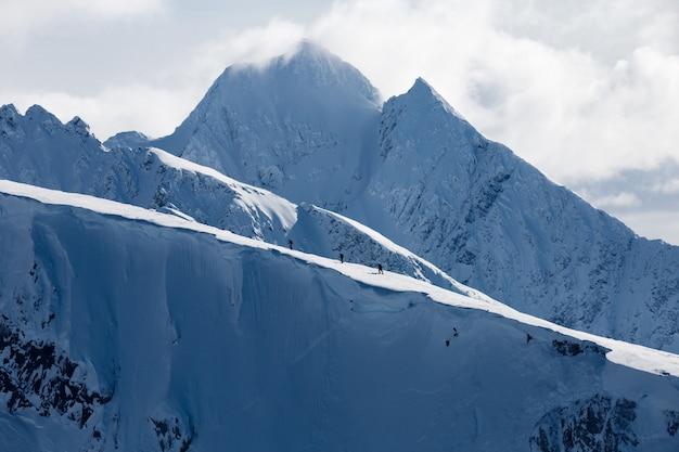 Tiro horizontal de altas montanhas cobertas de neve sob nuvens brancas e um grupo de pessoas caminhando