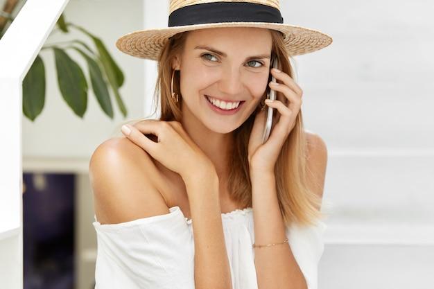 Tiro horizontal de aparência agradável usa chapéu e blusa branca.