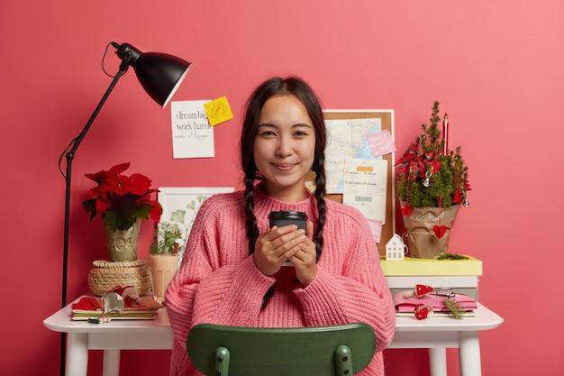 Tiro horizontal de atraente garota coreana segura café para viagem, se senta na cadeira perto de seu local de trabalho, termina de trabalhar, adesivos na parede rosa.